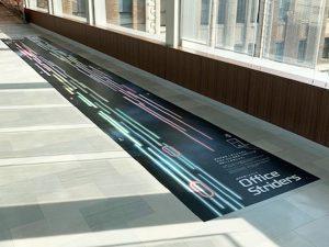 健康促進のデザインが印刷されたフロアシート。スマホを利用すれば、歩く速さの目安がわかります。(神奈川県庁にて)
